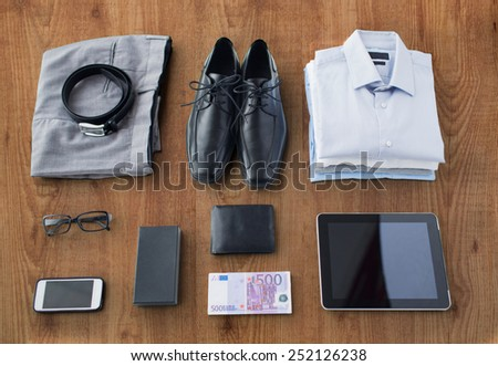 business, style, clothes and objects concept - close up of formal male clothes and personal stuff on wooden table at home - stock photo