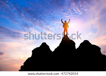 Business success concept.Silhouette of victory businessman on top of the mountain with sunset sky as background