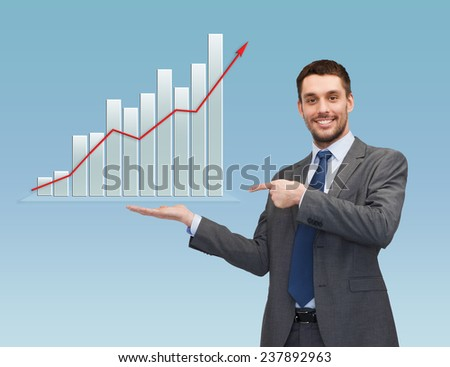 business, success, economics, and people concept - smiling young businessman pointing finger and showing growth chart on palm of his hand over blue background