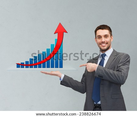 business, success, economics, and people concept - smiling young businessman pointing finger and showing growth chart on palm of his hand over gray background