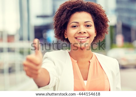business, success, gesture and people concept - young smiling african american businesswoman showing thumbs uo in city - stock photo