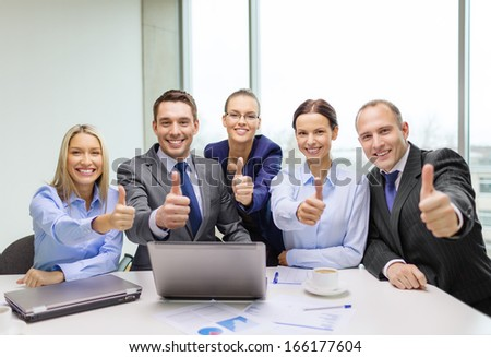 business, success, technology and office concept - smiling business team with laptop computer, papers and coffee showing thumbs up in office - stock photo
