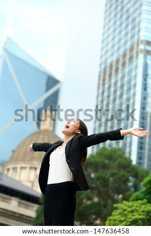 Business success with successful woman in Hong Kong celebrating business achievements with arms spread out winning. Young mixed race Chinese Asian / Caucasian female professional in Hong Kong central. - stock photo
