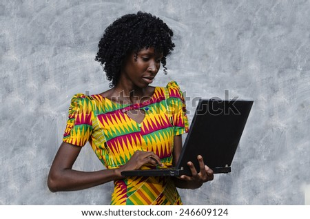 Business Symbols: African Woman Holding Laptop Technology - stock photo