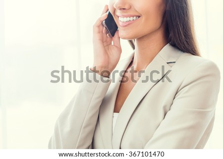 Business talk. Cropped image of confident young businesswoman in suit talking on the mobile phone and smiling - stock photo