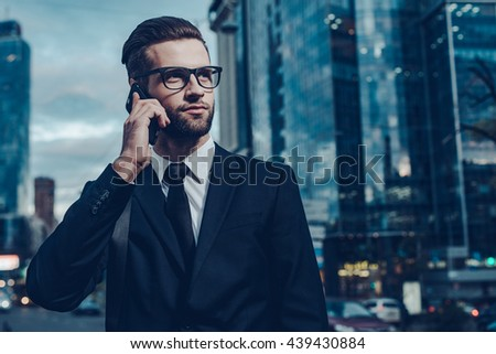 Business talk. Night time image of confident young man in full suit talking on the mobile phone and looking away while standing outdoors with cityscape in the background - stock photo
