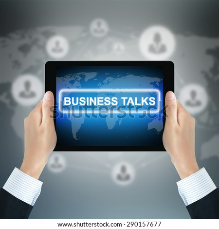 BUSINESS TALKS message on tablet pc screen held by businessman hands