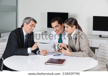 Business tax consultant with tablet computer in a meeting in the office - stock photo