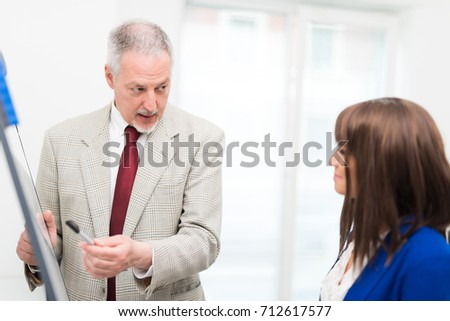Business teacher, senior businessman explaining financial concepts to a businesswoman