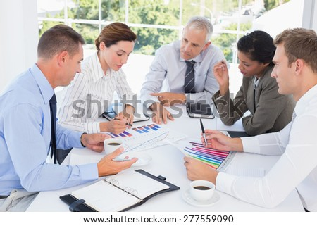 Business team analyzing bar chart graphs in the office - stock photo