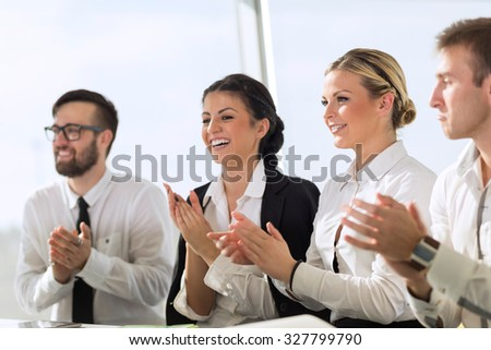 Business team applauding a colleague on a successful presentation - stock photo