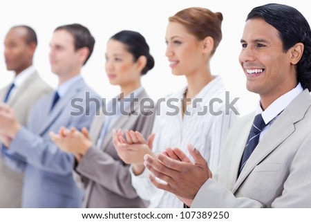 Business team applauding while looking towards the left side with focus on the first man against white background - stock photo