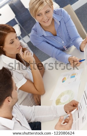 Business team at meeting, reviewing documents, chart, diagram, elevated view. - stock photo