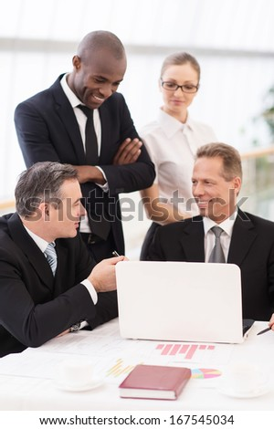 Business team at meeting. Two cheerful mature man in formalwear sitting at the table and communicating while two another people standing close to them  - stock photo