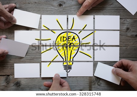Business team brainstorming and finding a solution or good idea with light bulb drawing on business card paper - stock photo