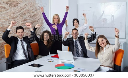 Business team celebrating a triumph in office with arms up