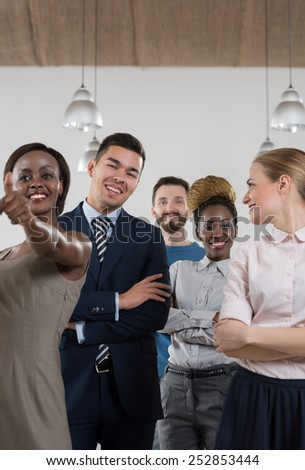 Business team celebrating a triumph with thumbs up - stock photo