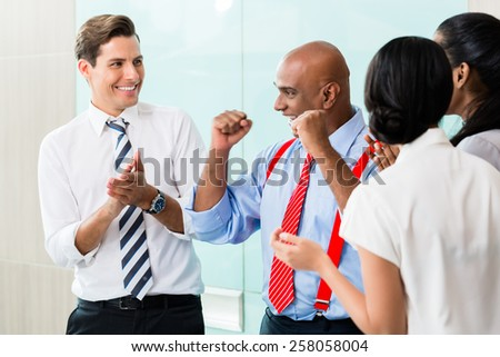 Business team celebrating success applauding and shaking fists - stock photo