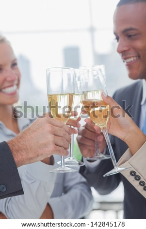 Business team celebrating with champagne and clinking glasses in he office - stock photo