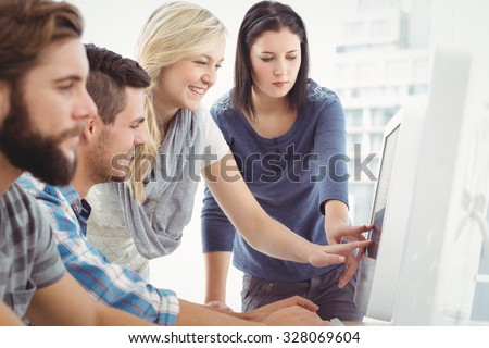 Business team discussing at computer desk in office - stock photo