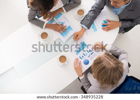 Business team discussing financial diagram, view from above