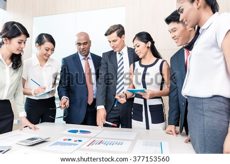 Business team discussing graphs and numbers in meeting, men and women of Chinese, Caucasian, Indonesian, and Indian ethnicity - stock photo