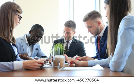 Business team discussing together business plans in office - stock photo