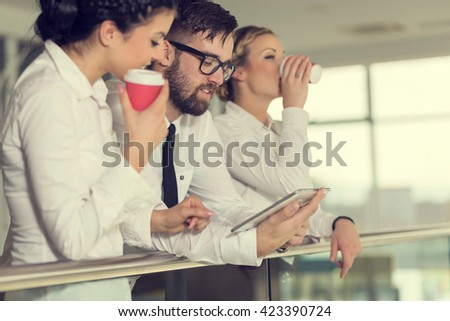 Business team discussing work related matters, standing in an modern office building hall, holding a tablet computer and drinking coffee - stock photo