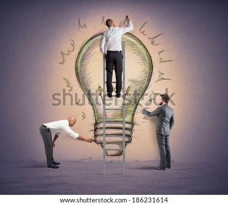 Business team drawing a new idea in a wall - stock photo