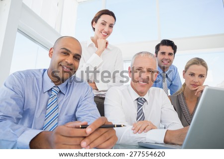 Business team during meeting smiling at camera in the office - stock photo