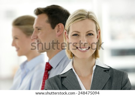 Business team - Focus on executive woman looking at camera - stock photo