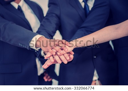 Business team. Four Confident businessman fold their arms tightly to each other in the office close up - stock photo