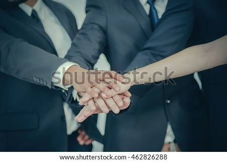 Business team. Four Confident businessman fold their arms tightly to each other in the office close up