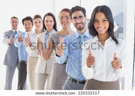 Business team giving thumbs up while smiling at work