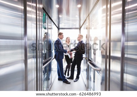 people in elevator. business team group going on elevator. people in a large glass elevator