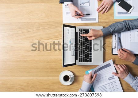 Business team hands at work with financial reports and a laptop, blank copy-space on left, top view