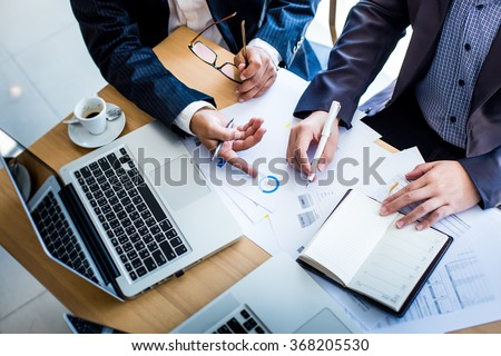 Business team hands at working with plan on office desk and modern digital computer laptop. Top view shot.