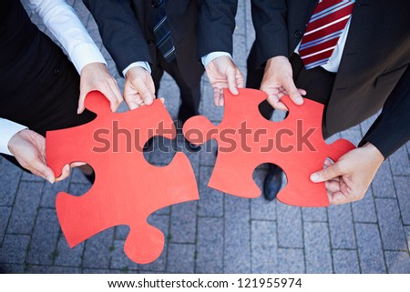 Business team hands holding two oversized red jigsaw puzzle pieces - stock photo
