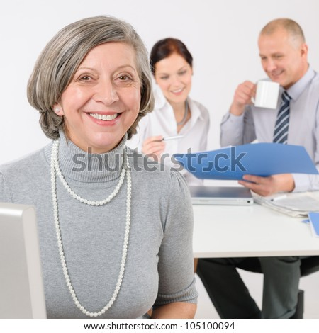 Business team happy senior businesswoman with attractive colleagues looking file - stock photo