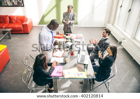 Business team having a meeting in a office, afro-american man exulting and his colleagues clapping hands - Successful businessman getting a promotion at work - stock photo