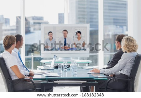 Business team having video conference with another business team in office - stock photo
