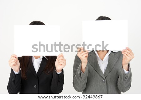business team holding a whiteboard hiding their face