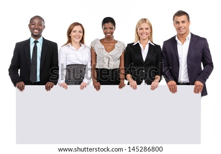 Business team holding board looking at camera - stock photo