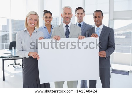 Business team holding large blank poster and smiling at camera - stock photo