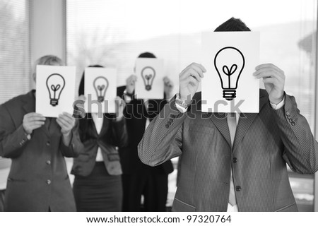 Business team holding light bulb - stock photo