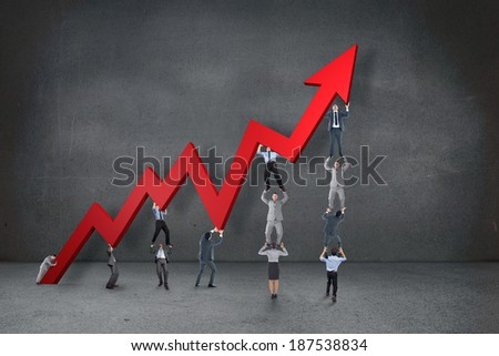 Business team holding up arrow against grey room