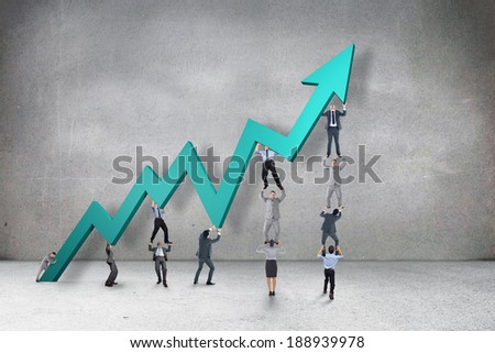 Business team holding up arrow against grey room - stock photo