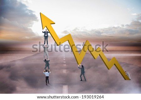 Business team holding up arrow against road leading out to the horizon - stock photo