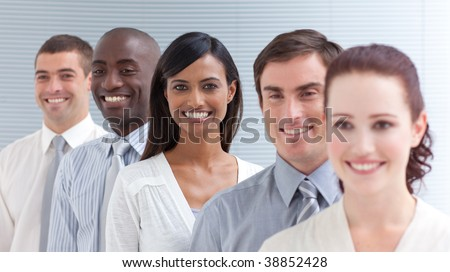 Business team in a line smiling at the camera. Focus on a Indian woman