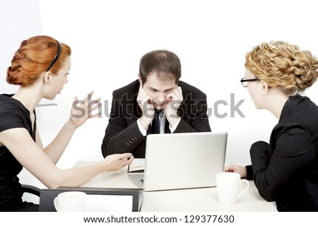 Business team in a serious meeting with the male leader staring dejectedly at his laptop while a female colleague explains something gesturing with her hands